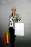 Mature woman shopping. Attractive mature woman showing off her shopping bags Stock Photo