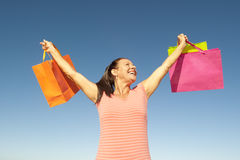 Mature woman with shopping bags outdoor. Attractive and happy looking mature woman holding up colourful shopping bags, isolated with blue sky as background and Stock Photography