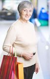 Mature woman with shopping bags. Portrait of happy woman with paperbags looking at camera in the mall Royalty Free Stock Photo