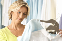 Mature woman shopping in clothes shop, comparing two tops on coathangers, close-up Stock Photo