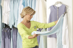 Mature woman shopping in clothes shop, comparing two tops on coathangers, side view Stock Photography