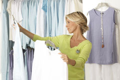 Mature woman shopping in clothes shop, comparing two tops on coathangers, side view Stock Photos