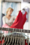 Mature woman shopping in clothes shop, holding red top, focus on clothes rail in foreground (tilt) Royalty Free Stock Photo
