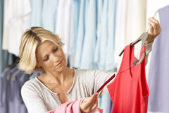 Mature woman shopping in clothes shop, holding red vest top on coathanger, checking price tag, smiling Stock Photos