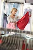 Mature woman shopping in clothes shop, holding red vest top, thinking, focus on background (tilt) Stock Images