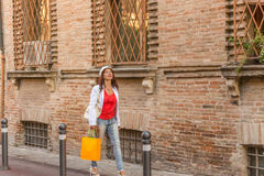 Mature woman shopping. And looking upwards while  walking the streets of Italian city Stock Image
