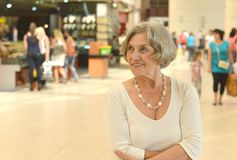 Mature  woman in shopping mall. Beautiful older woman in a shopping center Royalty Free Stock Image
