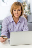 Mature woman shopping online at home during Christmas Stock Photo