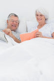 Mature woman showing her book to husband Royalty Free Stock Images