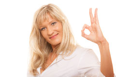 Mature woman showing ok sign hand gesture isolated. Business, gesture and office concept. Happy mature woman showing ok sign isolated Royalty Free Stock Photography