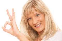 Mature woman showing ok sign hand gesture isolated. Business, gesture and office concept. Happy mature woman showing ok sign isolated Royalty Free Stock Image