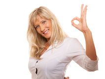 Mature woman showing ok sign hand gesture isolated. Business, gesture and office concept. Happy mature woman showing ok sign isolated Royalty Free Stock Images