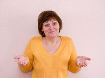 Mature woman shrugs and smiling Stock Image