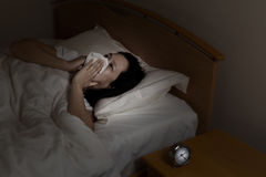 Mature woman sick while lying in bed at night time Royalty Free Stock Images
