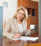 Mature woman signing documents Royalty Free Stock Photo