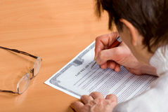 Mature woman signing Last Will royalty free stock photo