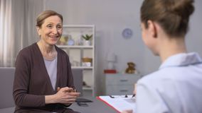 Mature woman sincerely rejoicing hearing good news about her health from doctor. Stock footage stock footage