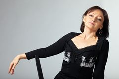 Mature woman sit on chair in lace jacket Stock Photography