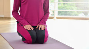 Mature woman sit on the mat on the knees. Healthy fitness concept with active lifestyle Royalty Free Stock Image