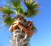 Mature woman sits on palm tree, scared Stock Photography