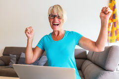 Mature woman sits rejoicing in front of a laptop. Picture of a mature woman sits who is rejoicing with raised hands in front of a laptop Royalty Free Stock Photo