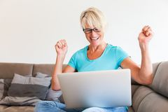 Mature woman sits who is rejoicing with raised hands in front of a laptop. Picture of a mature woman sits who is rejoicing with raised hands in front of a laptop Stock Photography