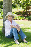 Mature woman sitting against a tree in park Stock Photo