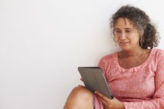 Mature Woman Sitting Against Wall Using Digital Tablet Stock Photos