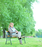 Mature woman sitting alone in the park Stock Photo