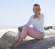 A mature woman sitting on a beach using a mobile phone Stock Image
