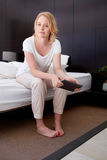 Mature woman sitting on bed with a digital tablet Stock Images