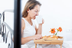 Mature woman sitting on   bed Stock Photo