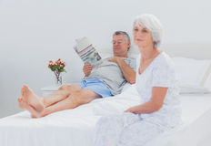 Mature woman sitting on bed. Mature women sitting on bed while husband is reading a newspaper on the background Royalty Free Stock Photos
