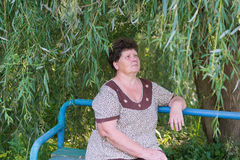 Mature woman sitting on the bench weeping willow. Mature woman with curly hair sitting on the bench weeping willow Royalty Free Stock Photo