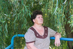 Mature woman sitting on the bench weeping willow. Mature woman with curly hair sitting on the bench weeping willow Royalty Free Stock Photos