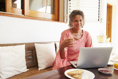 Mature Woman Sitting At Breakfast Table Using Laptop Royalty Free Stock Photos