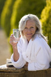 Mature woman sitting on chair outdoors, holding glass of water, smiling, portrait Royalty Free Stock Images