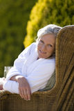 Mature woman sitting on chair outdoors, smiling, portrait Royalty Free Stock Photography