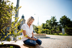 Mature woman sitting in a city park, operating smartphone. Royalty Free Stock Images