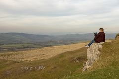 Mature woman sitting on cliff top overlooking rural view. Of hillsides stock photography