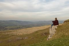 Mature woman sitting on cliff top overlooking rural view. Of mountains royalty free stock image