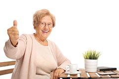 Mature woman sitting at a coffee table and making a thumb up sig royalty free stock photo