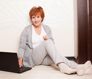 Mature Woman sitting on floor with laptop Stock Photo