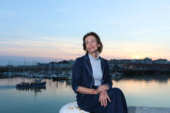 Mature woman sitting by the harbour. Elegant mature woman sitting by the harbour at sunset Stock Photos