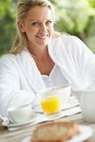 Mature woman sitting at her breakfast table Stock Photos