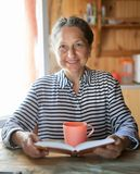 Mature  woman  reading in  kitchen. Mature  woman  sitting in  kitchen reading and drinking tea royalty free stock image