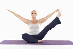 Mature woman sitting on mat and doing yoga with arms outstretched Royalty Free Stock Photography