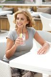 Mature woman sitting outdoors with a glass of water Stock Photos