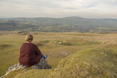 Mature woman sitting outdoors overlooking a view. Mature woman sitting outdoors overlooking rural view royalty free stock photo