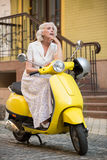 Mature woman sitting on scooter. Stock Photo
